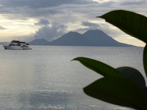 The dive boat is at peaceful anchor under the gaze of the volcanos