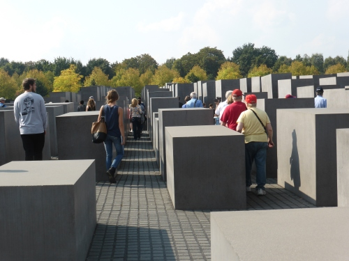 People walk silently through the memorialMost stelae tower above head height.