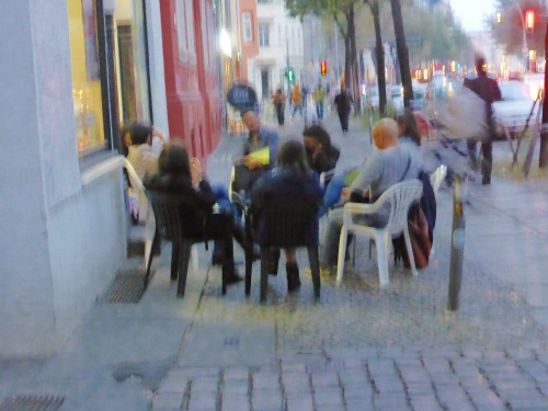 A impressionist photo of a surreal scene. An italian book group philosophising  chairs in a circle on the footpath.