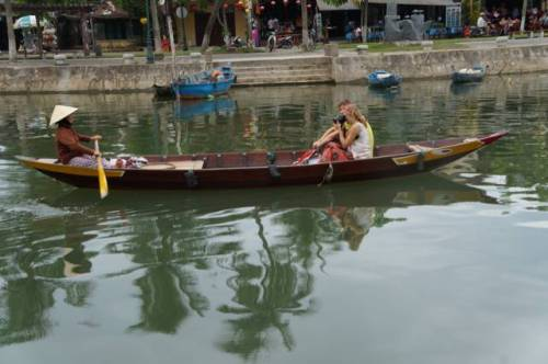 An older woman rows the tourists who photographer her